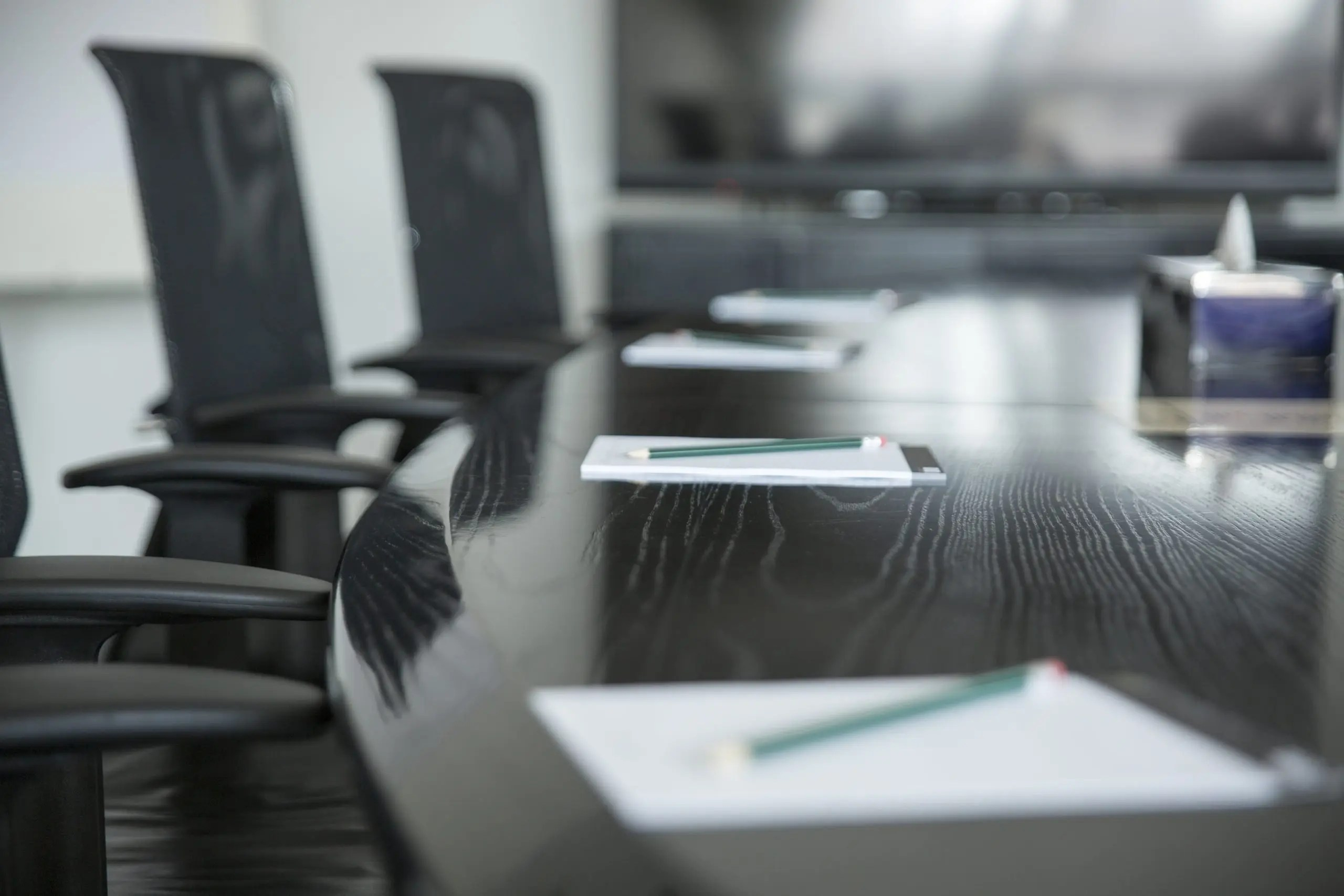 Empty Conference Room with paper and pencils in front of each seat - symbolizing a board meeting