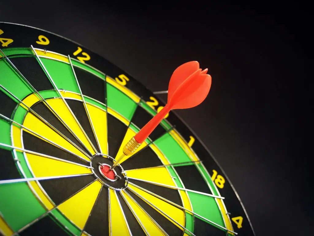 Black, green and yellow dartboard with a red dart in the bulls eye. Determining a good graduation rate is not as clear a target.