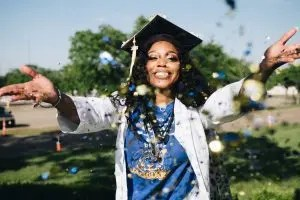 Graduating african american female student throwing confetti