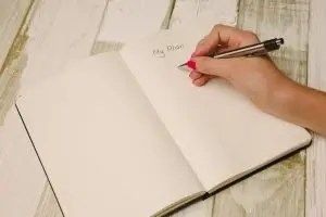 """This image is a hand with a pen over a notebook writing """"My plan."""" Planning is an important part of student success."""