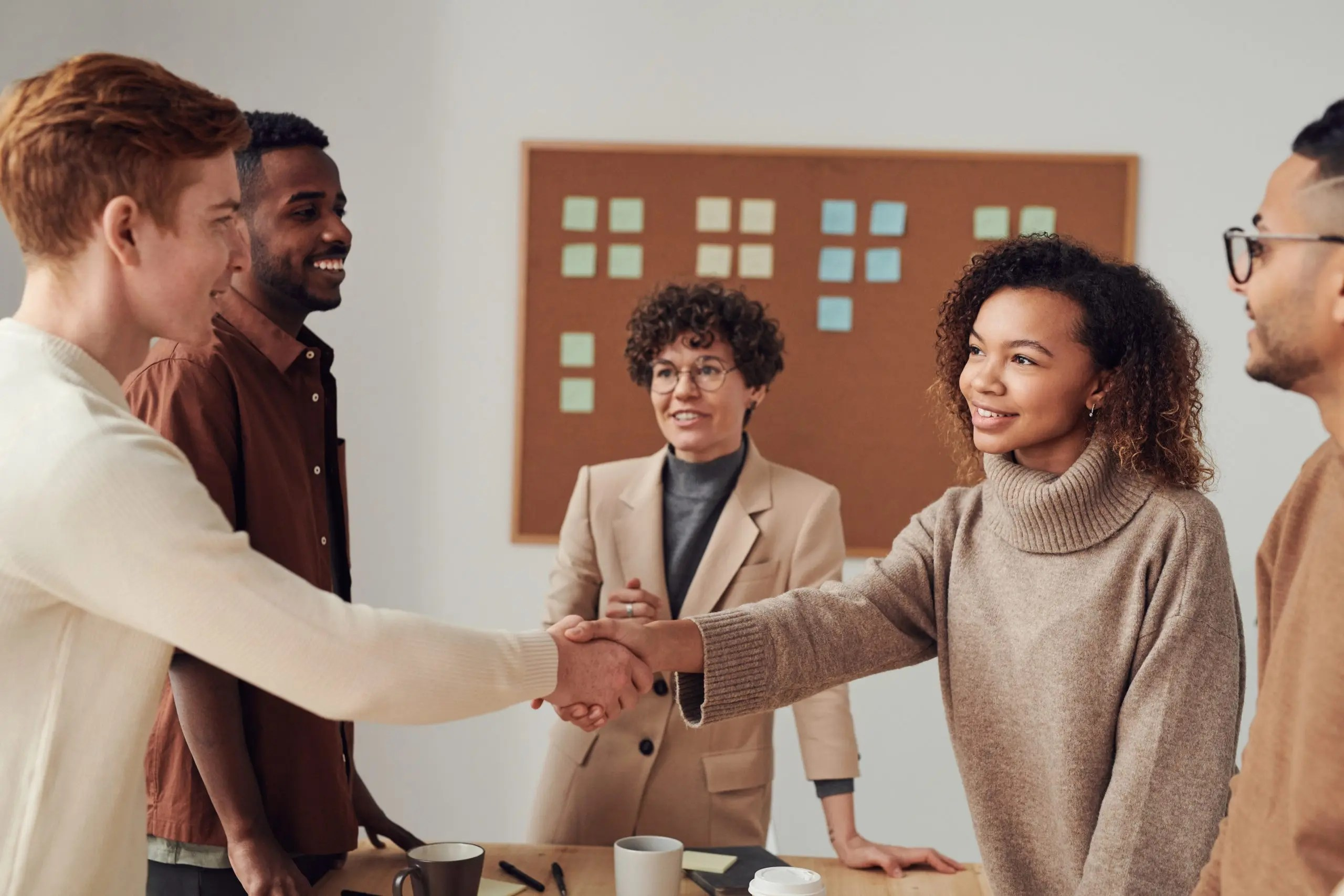 Multi-racial group of people with a man and woman shaking hands
