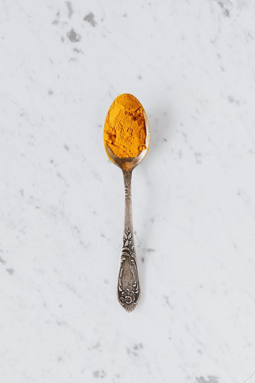 yellow turmeric powder in silver spoon