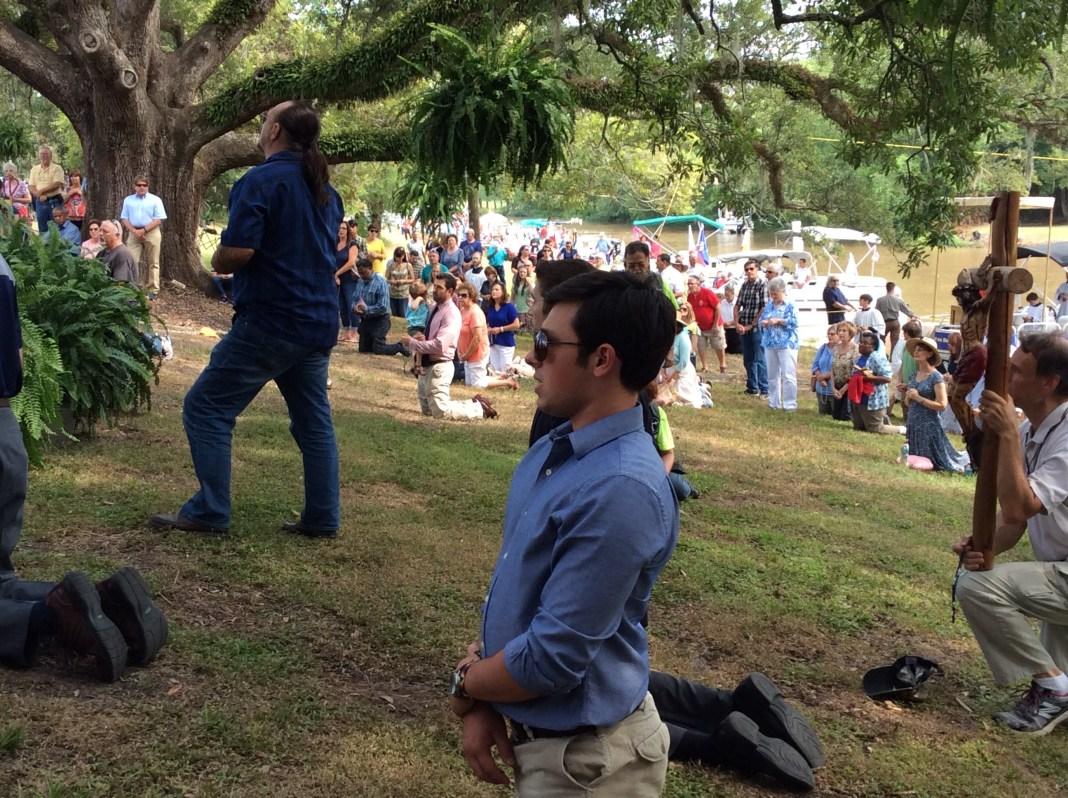 De rodillas rezando el Santo Rosario en frente al Santísimo Sacramento