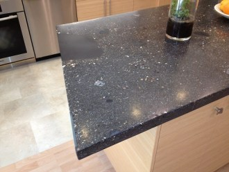 Concrete counter top with rocks and glass tiles incorporated.