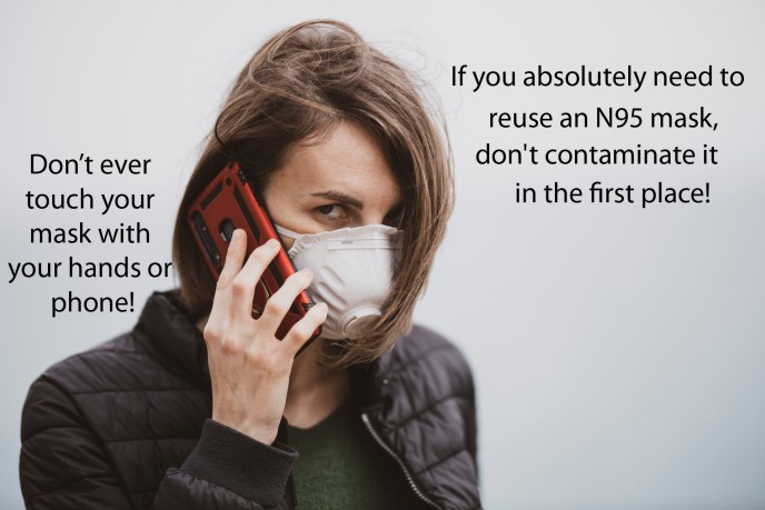 Woman holding a cell phone up to her N95 mask. Cell phones are highly contaminated surfaces, and bringing them in close proximity to a face mask will contaminate the face mask. Please do not contaminate face masks! Doing so increases the chance of self infection.