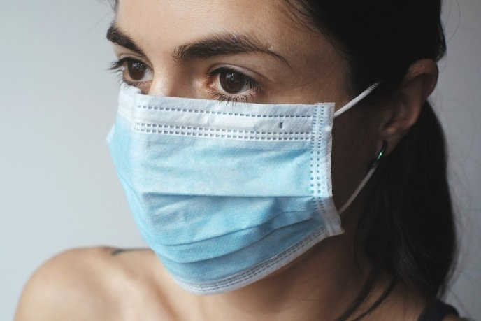 Woman wearing surgical mask to reduce her chance of COVID-19 infection. She is following coronavirus safety tips for her protection