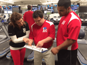 Evan and colleagues look at a sheet of paper in a binder while standing in a gym