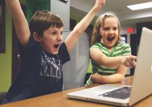 Children cheering by a computer