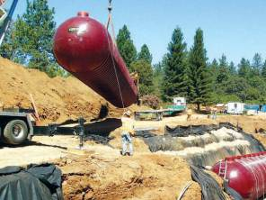 A crane lifts a Xerxes wastewater treatment tank into position