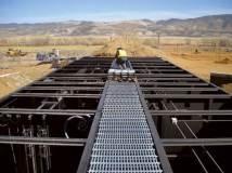 A worker installs walkway grating on an Ashbrook unit