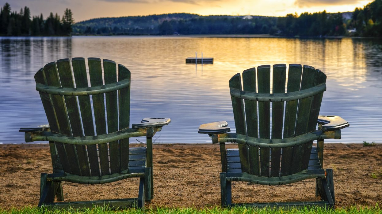 Two wooden chairs on beach of relaxing lake at sunset. Algonquin provincial park, Canada.