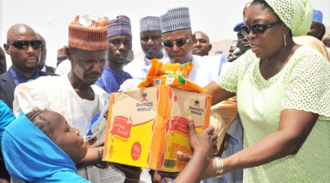 M.D. Dangote Foundation, Zouera Youssoufou, (Right) Presenting Food Items to one of The Beneficiary with A Bag  of Rice (Left) While Borno State Governor (Middle) Alhaji Kashim Shettima, At The Distribution of  Dangote Foundation Donate Foods Items for Ramadan to (IDP) Internal Displays People  of Bakkasi Camp in Maiduguri Borno State.
