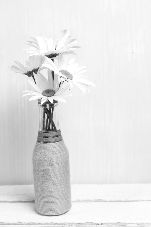 A bunch of daisies in a hessian covered glass bottle on a white background