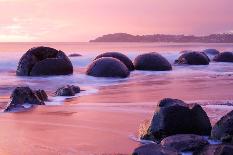 Moeraki boulders in new zealand under a pink sky