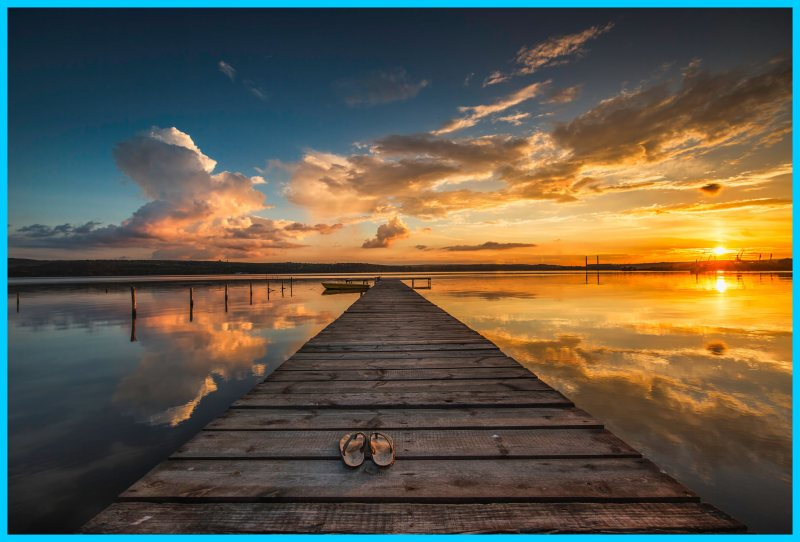 A wooden dock and boat with a lone pair of sandals. Over the sea at sunset.