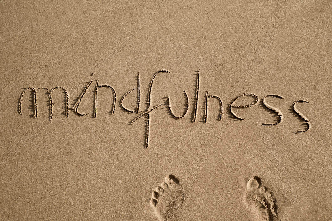 The word mindfulness written in light sand and a pair of human footprints