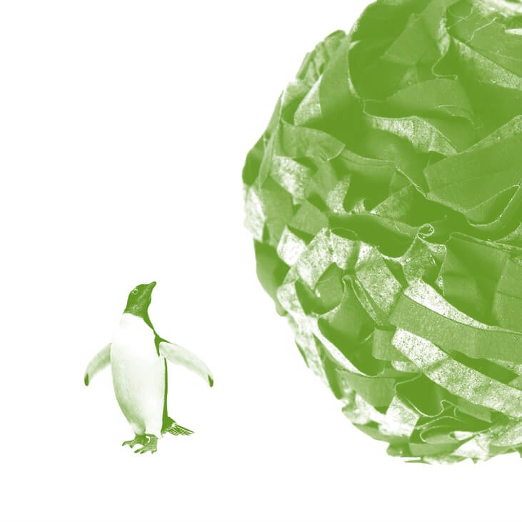 With a green filter, a penguin looks up at what looks like a huge ball of crumbled paper rolling towards it.