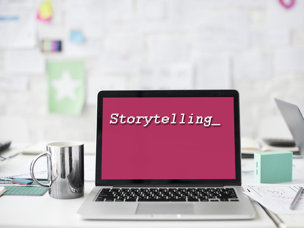 """Auf einem Laptop mit pinkem Hintergrund erscheint groß das Wort """"Storytelling"""""""