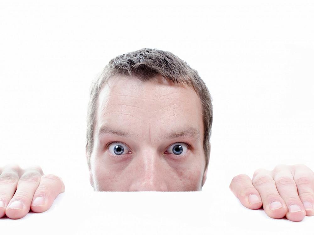 Verwirrt dreinblickender Mann halb unterm Tisch