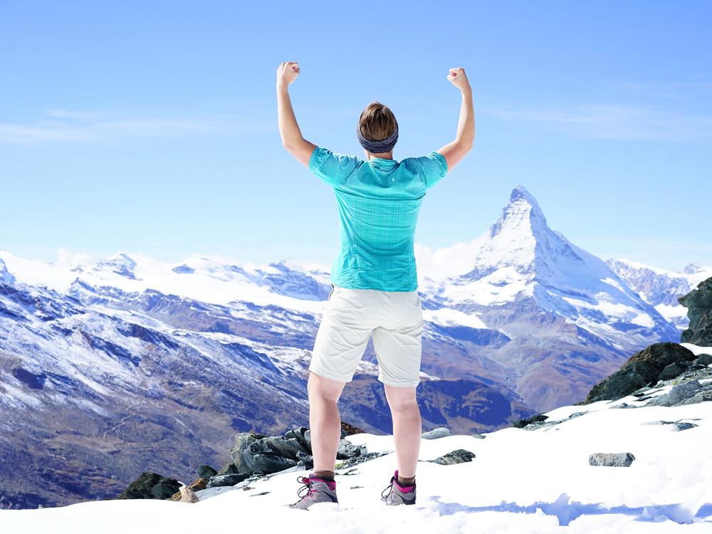Ein erfolgreicher Bergsteiger wirft triumpfierend die Arme in die Luft