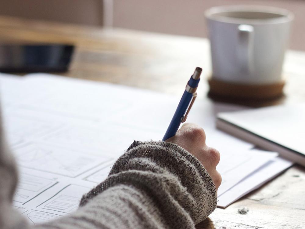 Eine Hand notiert etwas auf dem Papier, im Hintergrund steht Kaffee.