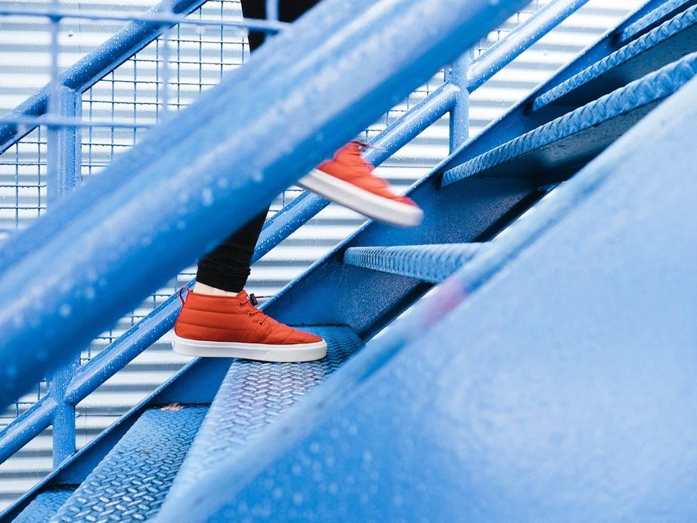Leuchtend rote Sneaker steigen eine bläuliche Treppe hinauf.