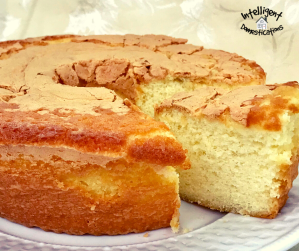 a pound cake on a white plate with on slice cut and slid out slightly revealing the moist inside