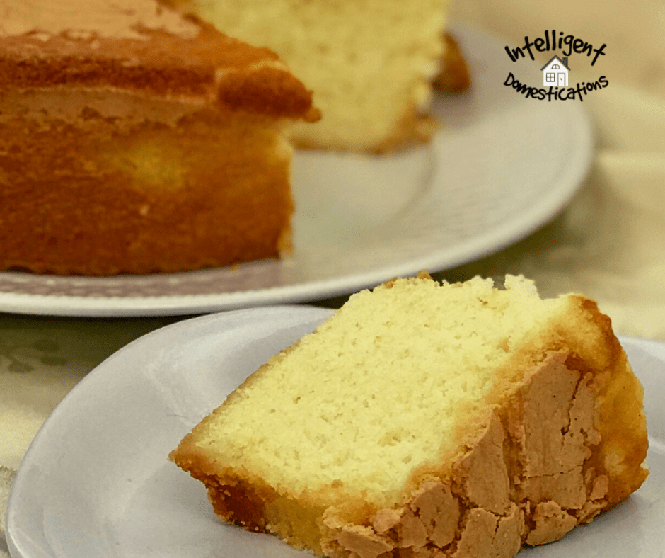a slice of Pound cake on a white dish in front of the whole cake