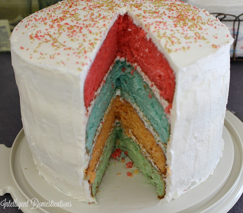 Rainbow Layer Cake recipe. How to make this four layer cake. Each layer is a different flavor. Spoiler alert, it's a Trick with Cake Mix cake! #trickswithcakemix #cakemix