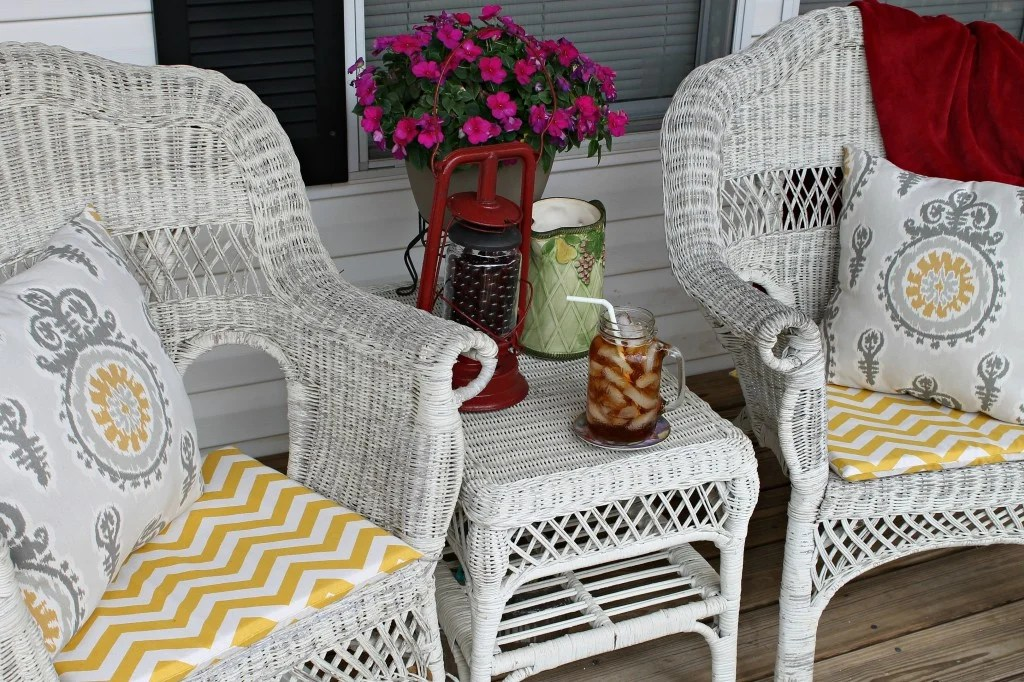 2.Cozy porch seating with added hand made cushions and pillows, flowers, Repurposed Solar Lantern and a special family afghan.intelligentdomestications.com