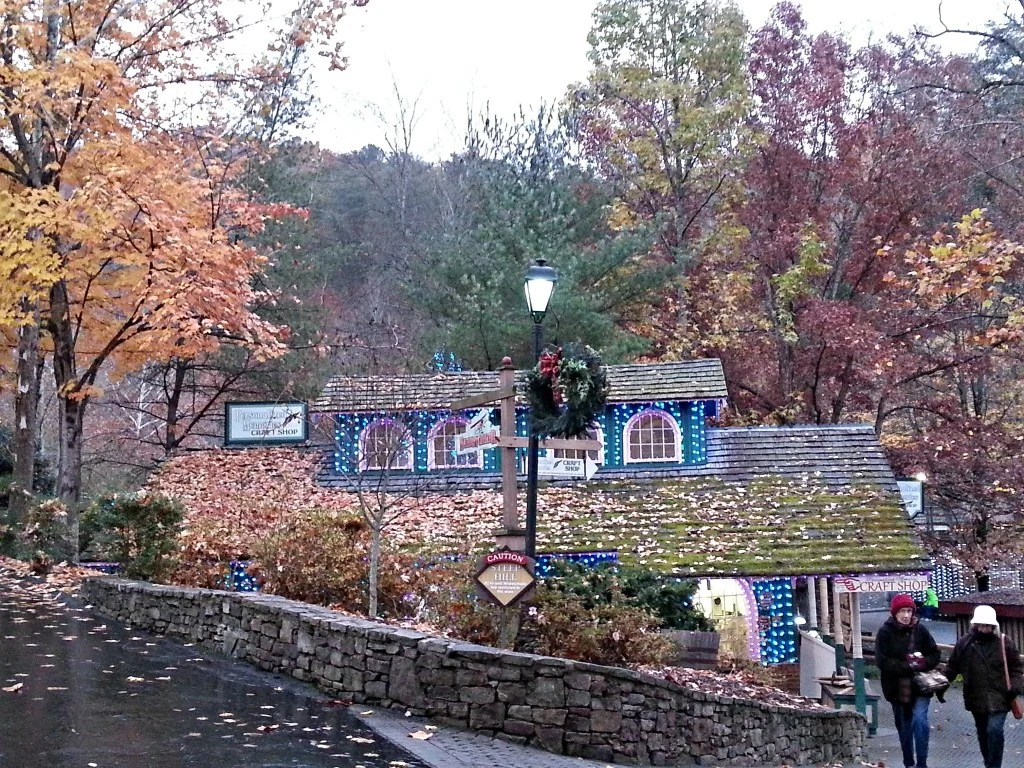 Dollywood's grassy roof craft shop outlined by Fall trees and lit up with Christmas lights