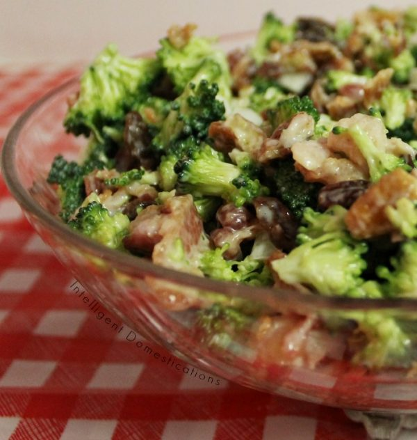 Broccoli Bacon Salad in a clear glass bowl on a table with a red and white checkered tablecloth