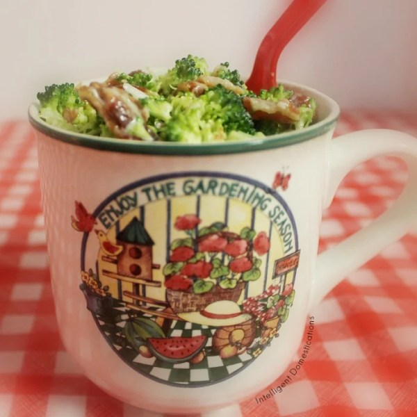 Broccoli Bacon Salad served in a mug with a handle and a summertime design on the front with a red plastic spoon tucked into the salad
