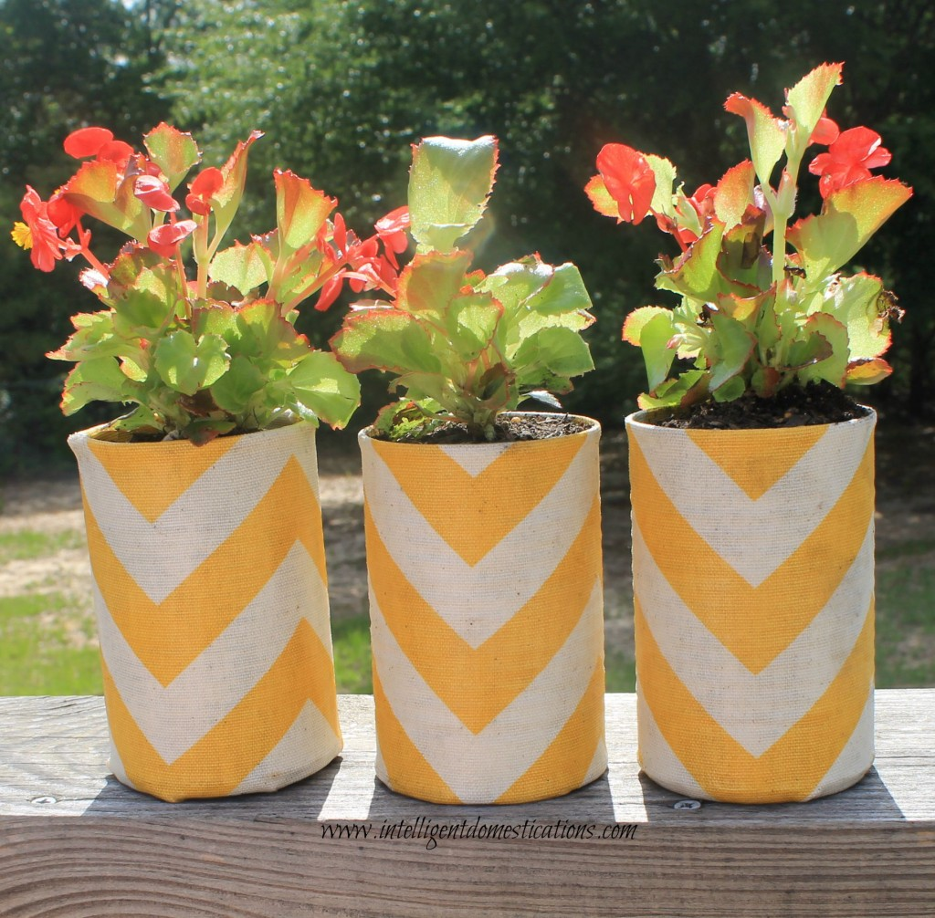 Repurposed vegetable cans into fabric covered  flower pots to match your porch pillows.www.intelligentdomestications.com