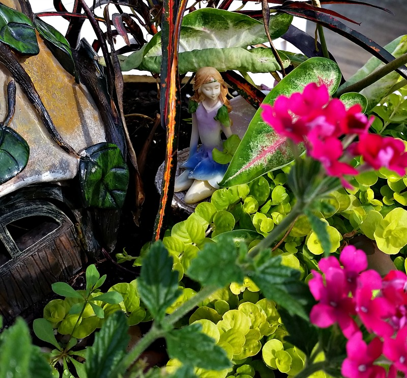 Our Fairy Garden Fairy Princess sitting on a tree stump next to her cottage