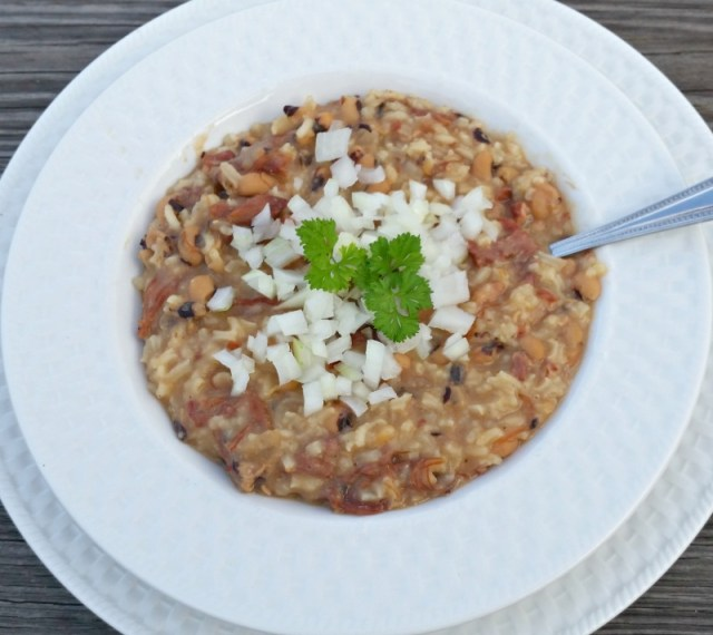 Black eye peas and rice in a white bowl with chopped onions and parsley on top