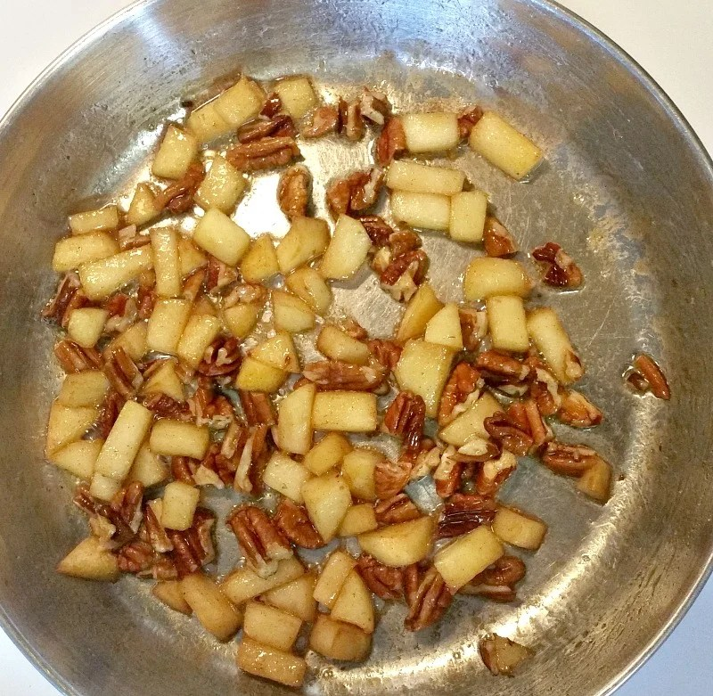 chopped apples and pecans cooking in a skillet