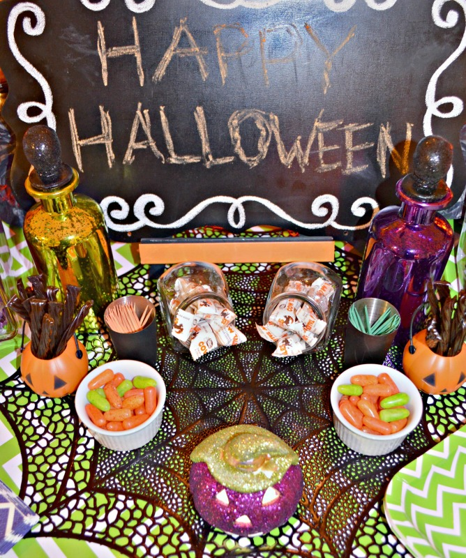 not-so-spooky-halloween-party-table-decorations-include-some-pretty-potion-bottles-candy-and-a-fun-chalkboard-announcement-inte