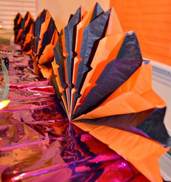 Orange and black paper fans for table decor. Halloween party decor ideas