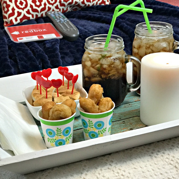 A tray of finger food  sitting on an ottoman in front of a sofa. The sofa has a cozy blanket, a Red Box movie and a TV remote control on it. There are chilled glasses with cola on the tray along with a candle.
