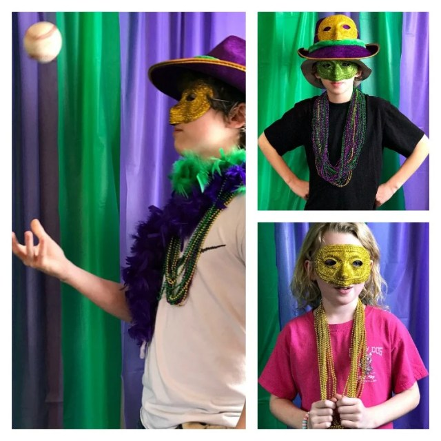 People posing in a Mardi gras party photo booth