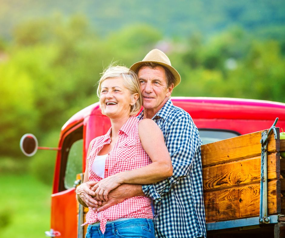 a couple holding hands standing next to a red pick up truck