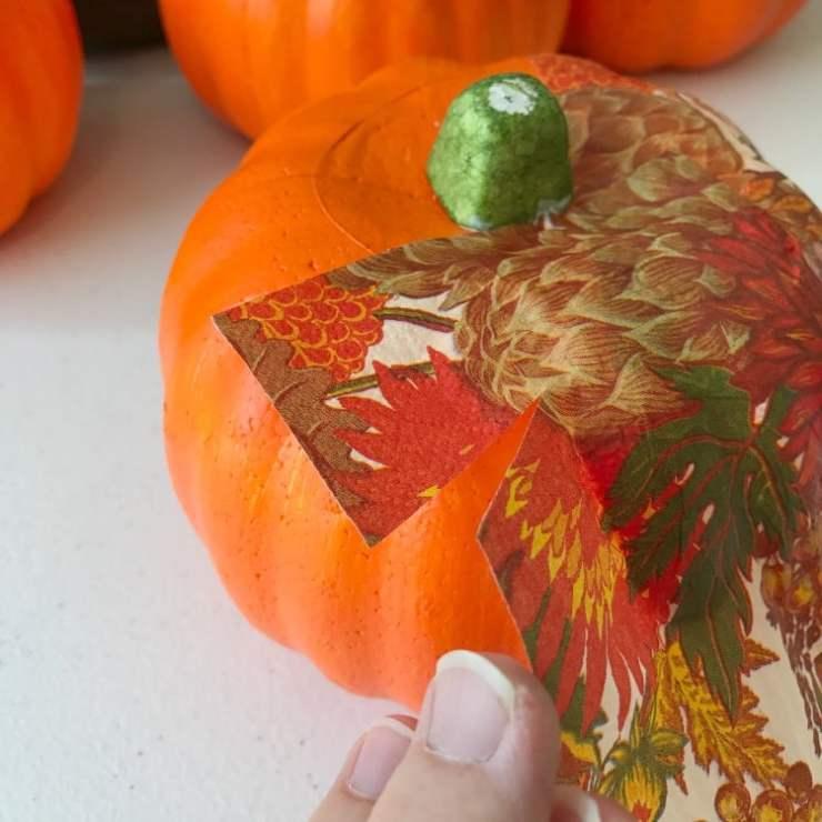 Fall Napkin being glued onto a Dollar Store Pumpkin