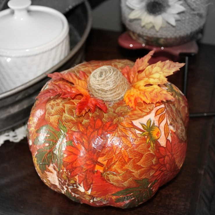 An fake pumpkin deecoupaged beautifully with a fall colors napkin and two fake leaves attached to the top. The stem is made of jute