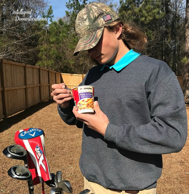 A young man with a golf bag eating a Jimmy Dean Simple Scrambles breakfast outside