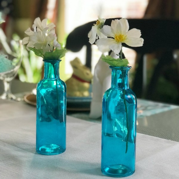 Simple Easter Table Decor. Easter Table Decorations. Blue Easter Table Decorations. Picture of see through blue bottles with flowers