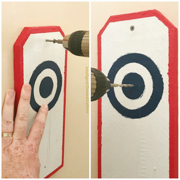 """How to install a Ring and Hook game in your garage. Use Two 2"""" deck screws to attach the bulls-eye board to the wall"""