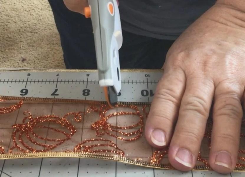 someone cutting orange ribbon using a rotary cutter