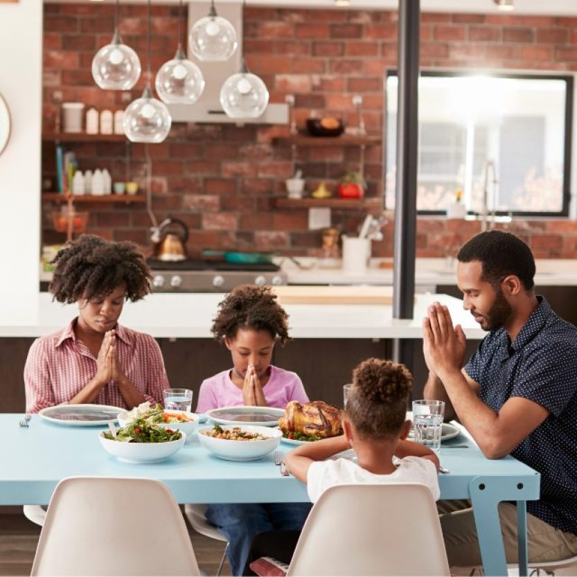 a family sitting at a table in front of their food saying their mealtime prayer