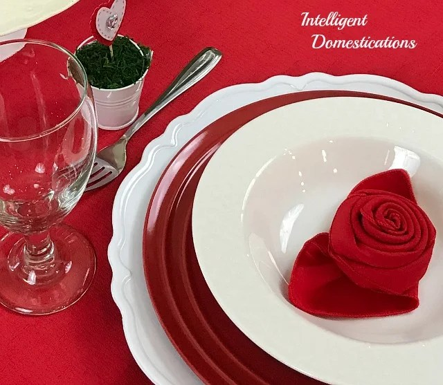 A Valentine's dinner table place setting with red and white dishes, a red tablecloth and water goblets